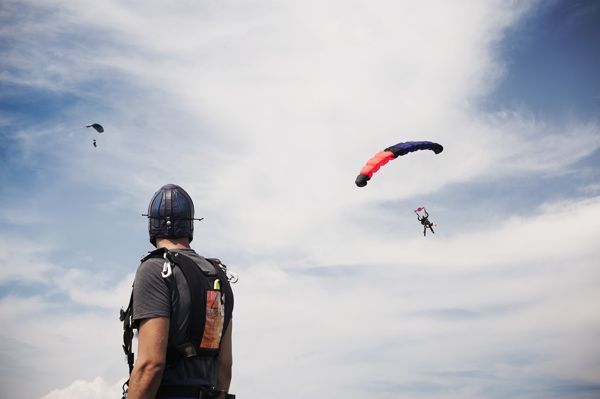 Skydiver watching others parachute in